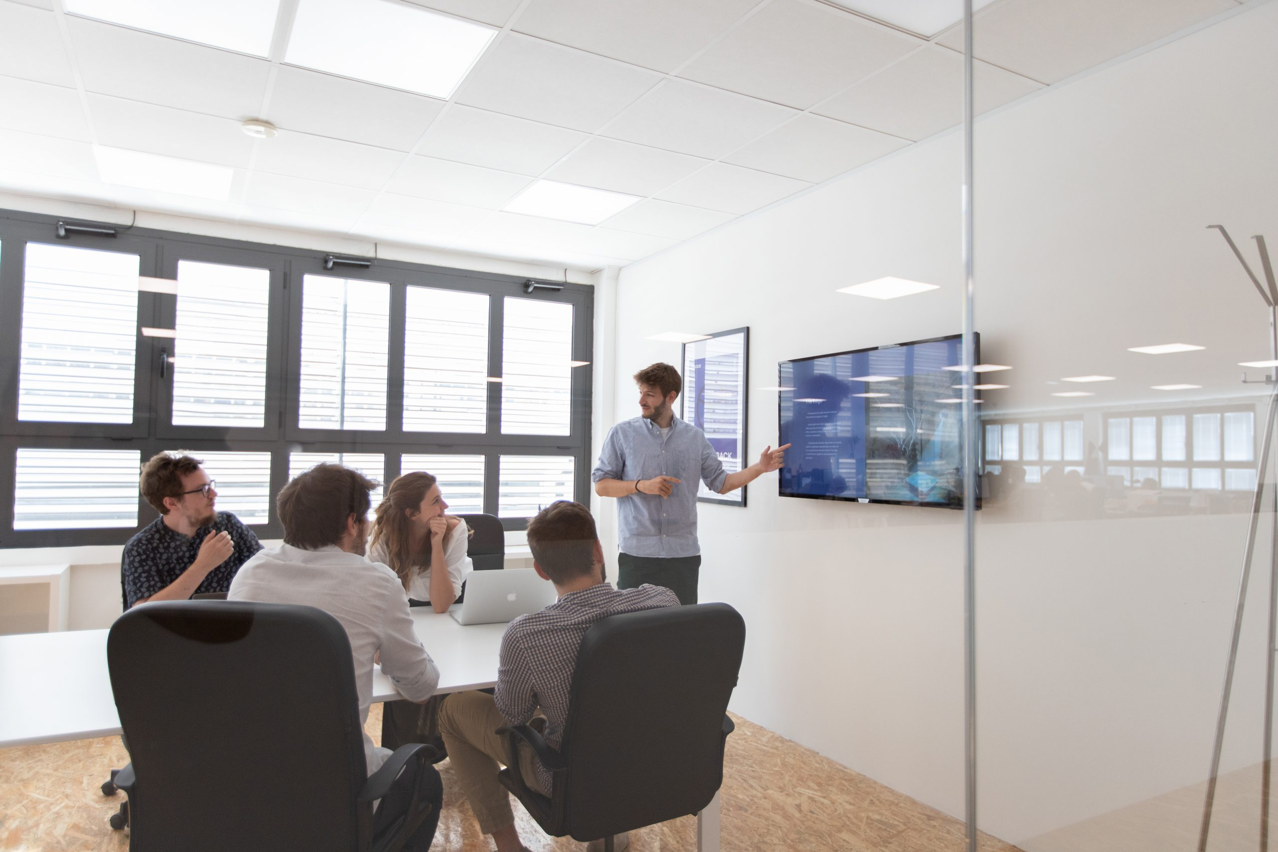 Team in sala riunioni che assiste ad una presentazione